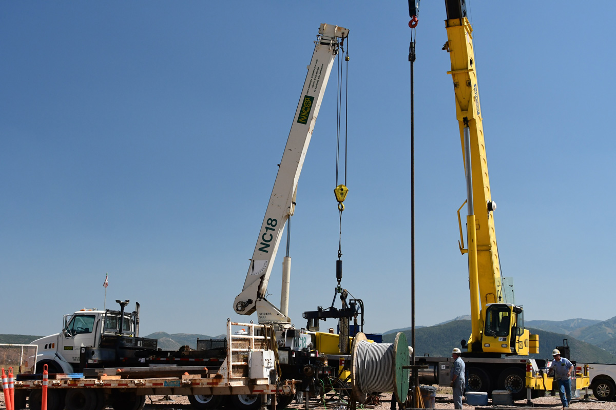 The removal of a deep well pump in the field using specialized equipment.